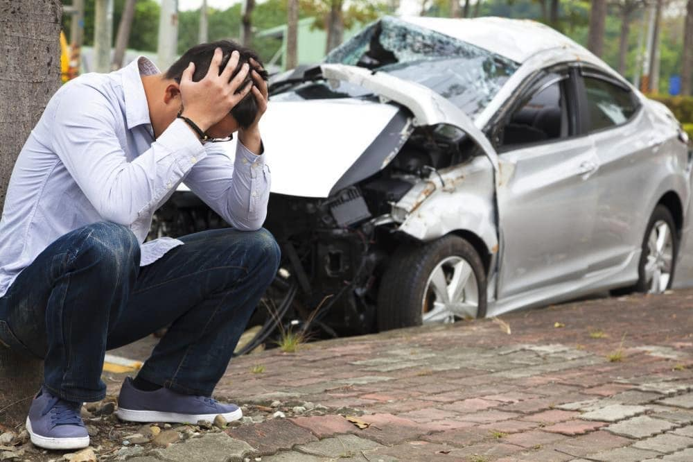 guy holding his head near his damaged vehicle after an accident