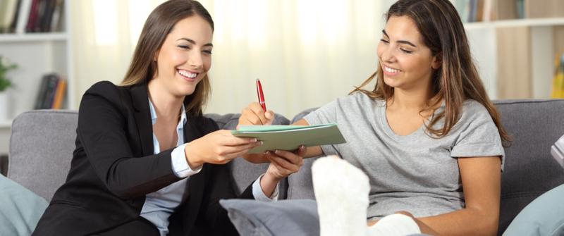 A woman happily signing a personal injury compensation agreement.