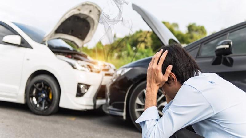 A man holding his head in his hands after a car accident.