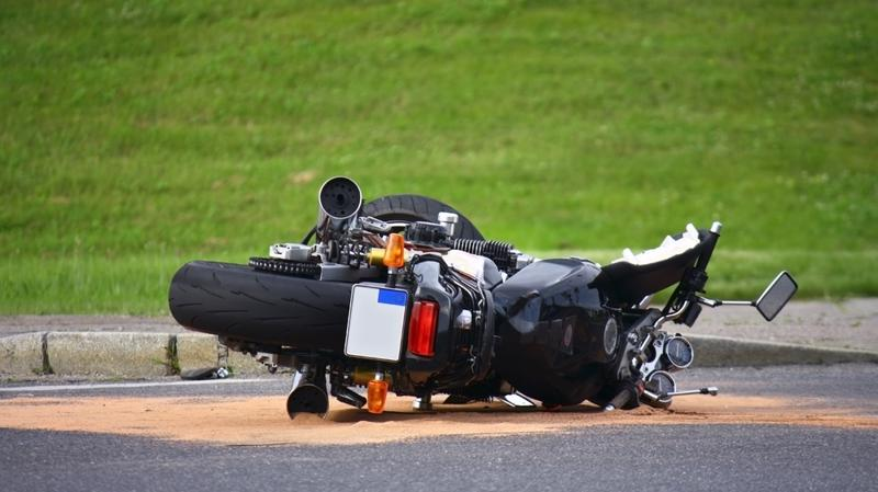 Lakeland Motorcycle Accident Lawyer shows a motorcycle lying on pavement after an accident near a field.