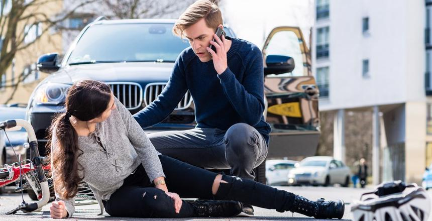 Lakeland Personal Injury Lawyer shows a woman hit by a car while bicycling lying in the road holding her leg while the man who hit her calls medical services.