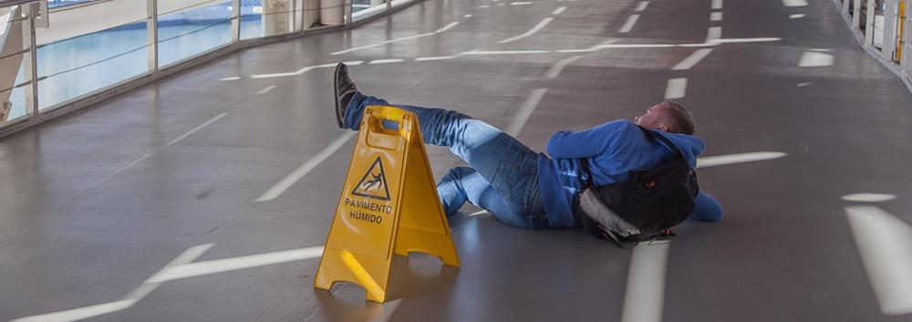Slip and Fall Attorney Lakeland shows a man in a hallway in a business slipping on a wet floor.