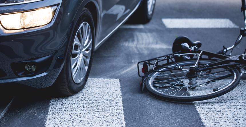 A bicycle lying in the road after an accident with a car.