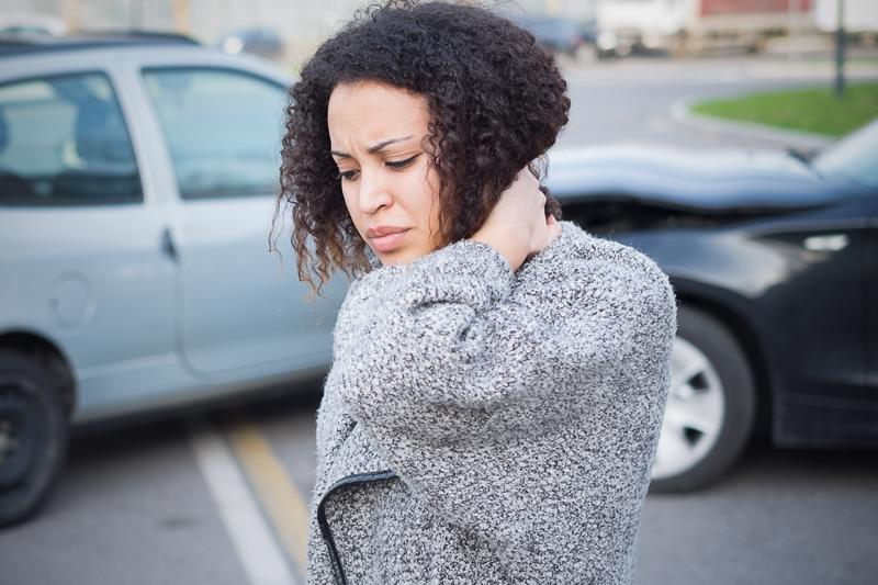 A woman holding her injured neck after a car accident.