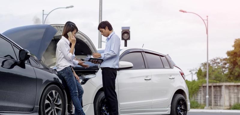 A car accident victim on the phone with an attorney while speaking with an insurance adjuster.