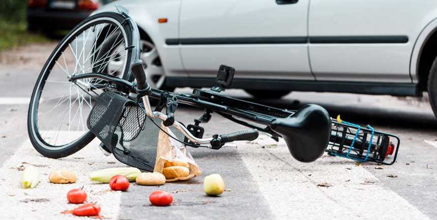 A car lying on its side surrounded by the contents of a spilled grocery bag after being struck by a car.