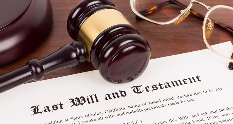 A desk with a last will and testament, gavel, and pair of reading glasses on it.