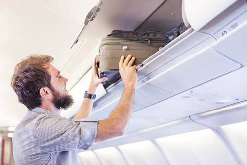 A man loading a suitcase into an overhead luggage compartment on a plane.