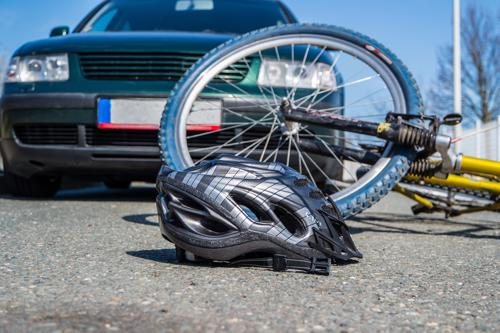 A yellow bicycle and grey helmet lying in the road after being hit by a green SUV.