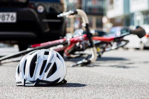 A white helmet and a red bicycle lying on asphalt in front of an SUV that struck the rider.
