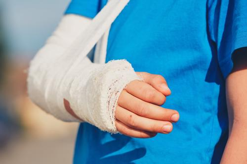 A child with their arm in a sling from an injury sustained on a playground.