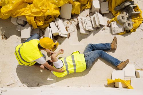 A man checking on a coworker who fell from a raised area at a construction site.