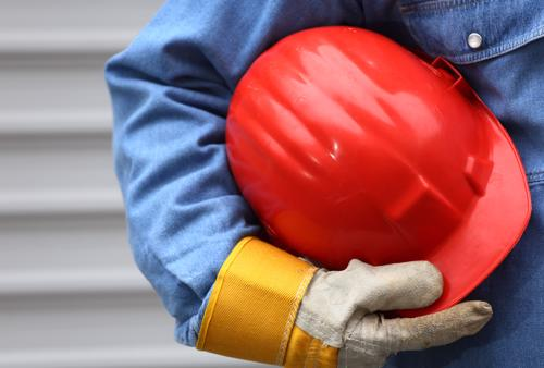 A person in coveralls holding a red construction helmet.
