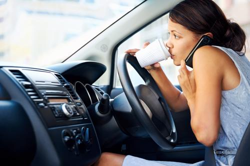 A woman attempting to drink coffee and speak on the phone while driving.