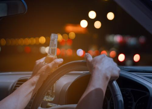 Hands on a steering wheel while holding a beer at night