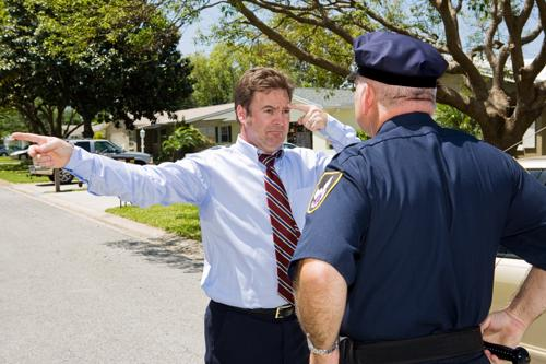 A man performing a field sobriety test in the afternoon for a police officer.