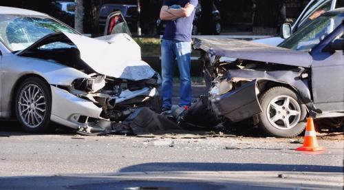 A man looking at the aftermath of a head-on accident.