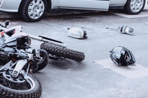A motorcycle, helmet, and car parts lying in the road after an accident.