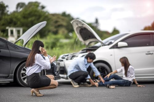 A woman calling a lawyer while a man tends to an injured person after a car accident in Town n Country, FL.