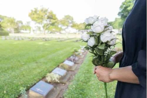 Image of young widow at graveside with white roses. Contact our Bayonet Point wrongful death lawyers.