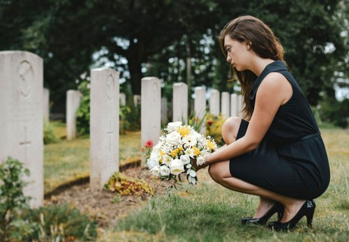 Image of young window placing flowers on grave. Contact a Bradenton wrongful death lawyer.
