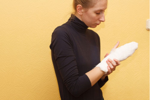 Image of young woman with bandaged hand. Contact an East Lake burn injury lawyer.