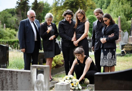 Image of family at grave. Contact an East Lake-Orient Park wrongful death lawyer today.
