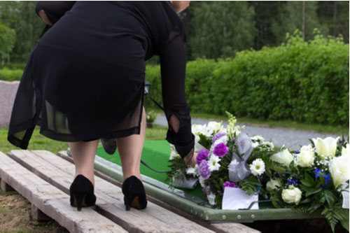 Image of woman laying flowers on grave. Contact a Lake Magdalene wrongful death lawyer.