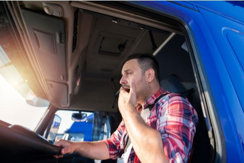 Image of a truck driver yawning. Driver fatigue is a factor in many truck accidents.