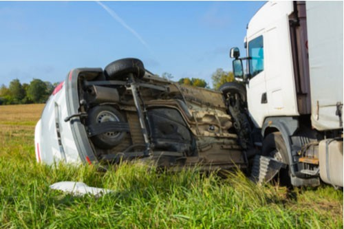 Image of truck accident with overturned car. Contact a Land O' Lakes truck accident lawyer at Winters & Yonker.