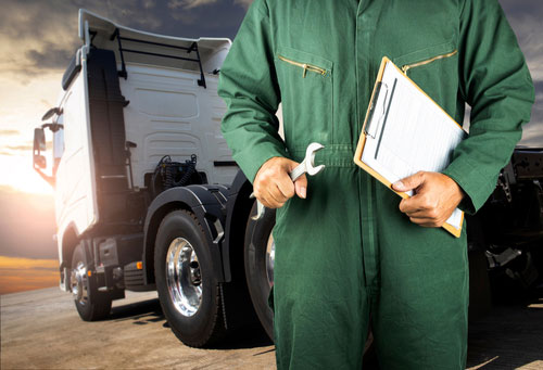Man with clipboard doing maintenance check on a commercial truck