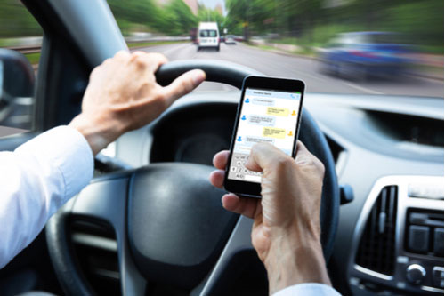 Man texting while driving. Dover distracted driving accident lawyer concept