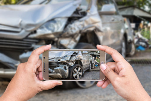 Woman using smartphone to take photo of car crash. Call our Dover drunk driving accident lawyers.