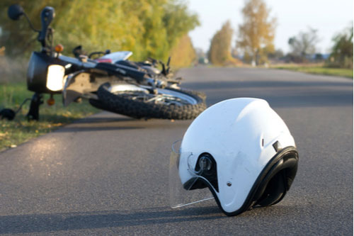 Helmet and motorcycle on road. Safety Harbor motorcycle accident lawyer concept