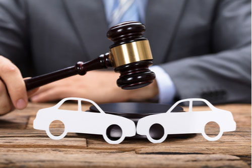 judge hitting mallet by paper cars on wooden table