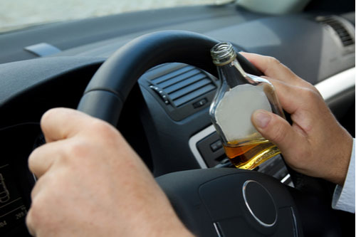 Driver with bottle of alcohol. Contact our Seffner drunk driving accident lawyers.