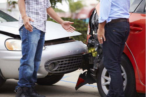 Two men talking about insurance after car wreck