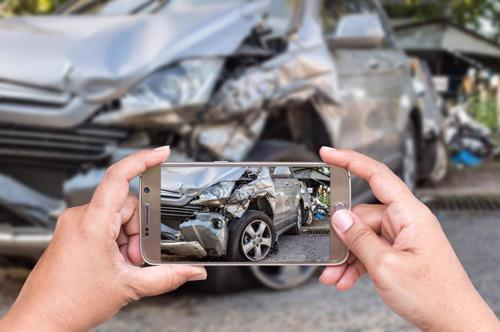 A man taking photos of his car after an accident in Parrish.