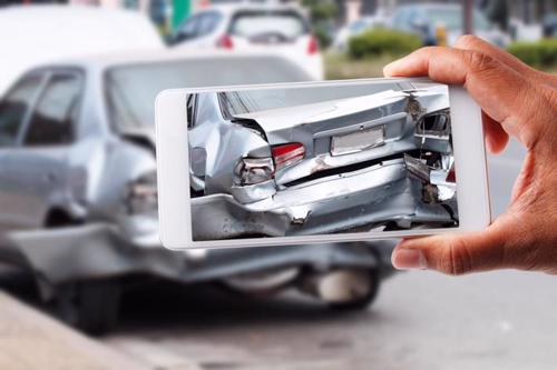 A man taking photos of a car accident to collect evidence.