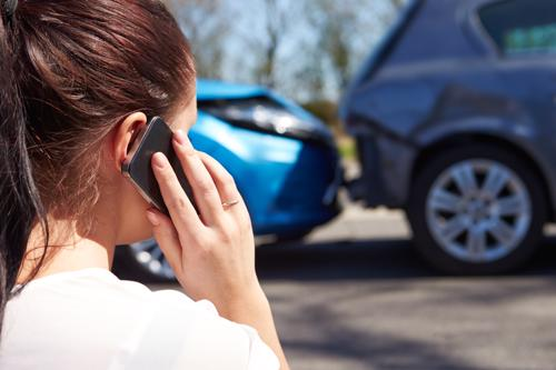 A woman calling the police after a car accident.